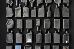 50 black plastic bottles and 1 blue plastic bottle on a black background