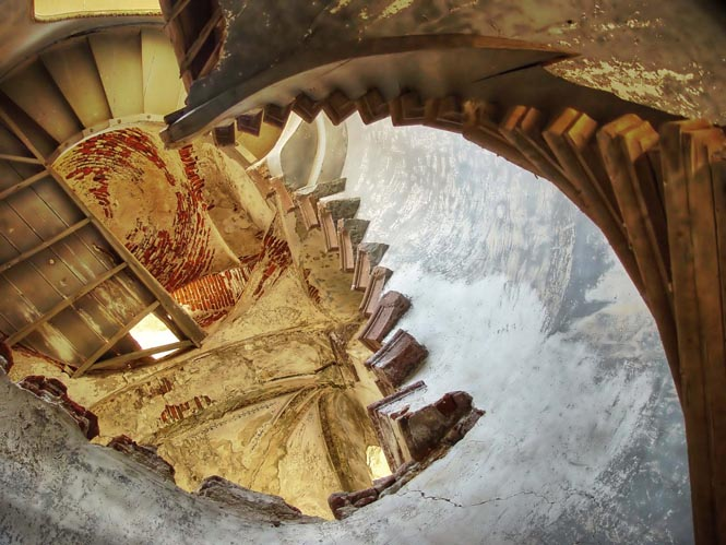 The underneath of a crumbling spiral staircase in the Cunda Greek Orthodox Cathedral, Ali Bey, Turkey